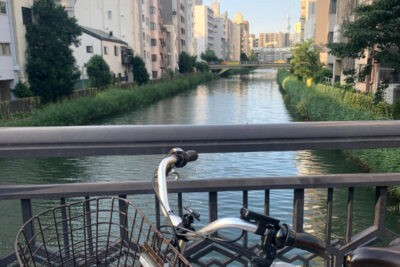 Electric bicycle with a small river in Tokyo and the Skytree in the background